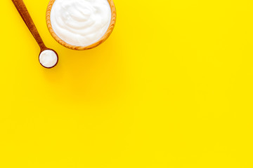 Healthy product, healthy meal. Greek yogurt in brown bowl near spoon on yellow background top view copy space