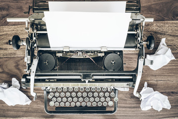 top view of vintage manual typewriter and crumpled sheets of paper on rustic wooden desk