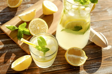 Iced lemonade pitcher, wooden juicer & one glass of cold citrus beverage with lemon slices, mint leaves & yellow straw on brown grunged wood textured table sunny day, background. Close up, copy space.