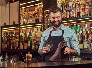 Cheerful stylish brutal barman is cleaning the glass with a cloth at bar counter background.