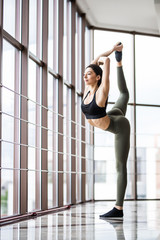Beautiful young woman practices yoga asana Natarajasana pose at the yoga studio
