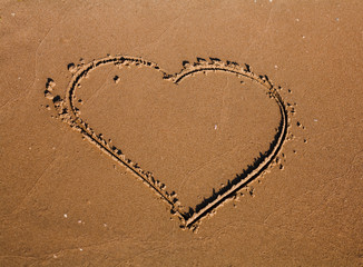 A drawing of a heart on a yellow sand.