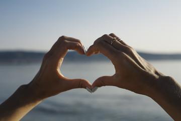 Female heart shaped hands against blue sea.