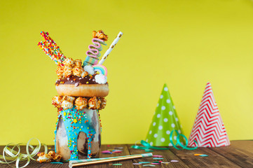 Chocolate freak shake topping with donut over yellow background