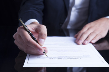 signing finance contract on dark table