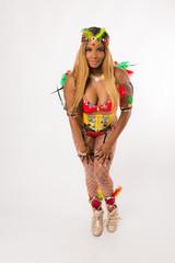 Fit young black woman in Carnaval costume and athletic shoes posing on clean white background
