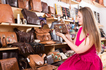 young blonde woman in shop chooses hand bags
