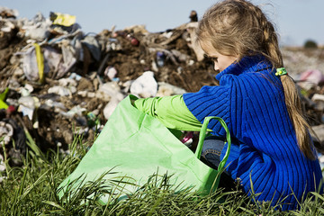 A poor child with pain in his soul sorts out trash in a landfill close-up