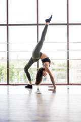 Young beauty slim Woman practicing yoga in a panoramic windows background in gym fitness hall