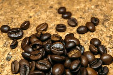 Fresh black coffe beans on cork table