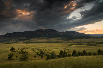 Dark clouds rolling over the Flatirons in Boulder, Colorado during sunset.