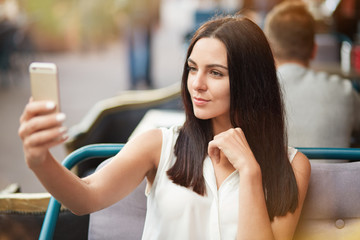 Good looking female model poses at camera of smart phone, makes selfie, spends leisure time at outdoor cafeteria alone or with lover. Elegant lady uses modern mobile phone for making photo of herself