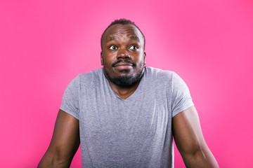 Thoughtful African man spreads his hands in the side standing on a pink
