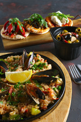 Set of tapas and paella with shrimps and mussels