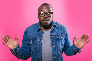 African man with glasses spread his hands to the side in surprise standing on a pink background