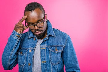 Thoughtful African man in glasses and jeans standing on a pink background thinking raised his hand to his head