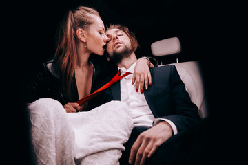 Passionate girl in a white Dress in the car salon with a guy in a suit and a red tie.sexy couple.feelings emotions.guy in a suit in the back seat with a girl