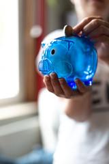 Junge Frau hält blaues Sparschwein in der Hand und wirft Geld hinein