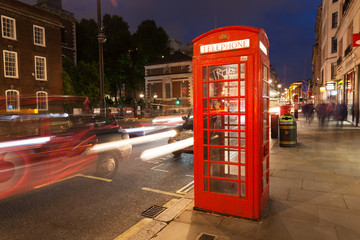 Popular tourist Red phone booth in night lights illumination in London, England, United Kingdom