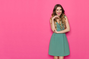 Beautiful Young Woman In Green Dress Is Posing With Hand On Chin