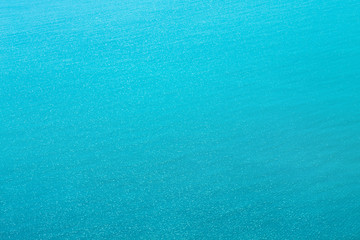 Sea texture of sparkling blue water. The surface is crystal water  with slight ripples  in sunny day.