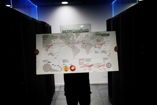 Iglesias holds a picture showing the global fiber optic interconnections inside the data center of the DataRush IT Services company in Malaga