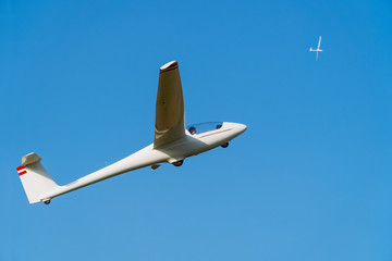 Two white gliders flying in clear blue sky. Concept of success, achievement of high goal