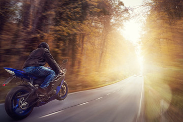 Motorbike on asphalt road in the forest