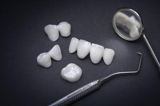 Dental tools and zircon dentures on a dark background - Ceramic veneers - lumineers