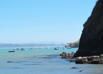 Blue Ocean, Seaweed and Rocky Cliffs in Bay with Fishing Boats in the Background