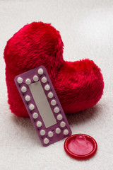Oral contraceptive pills condom on red heart