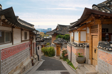 Traditional Korean style architecture at Bukchon Hanok Village with N Seoul Tower in background in Seoul, South Korea.