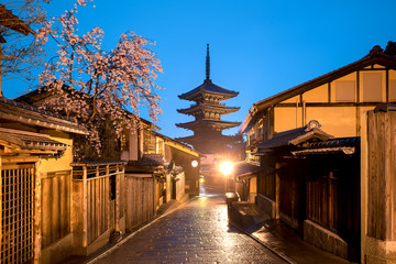 Japanese pagoda and old house with cherry blossom in Kyoto at twilight.