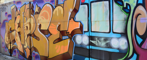Street art. Abstract background image of a full completed graffiti painting in beige and orange tones with the subway train