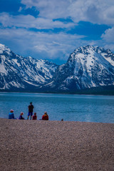 Group of tourist sitting in the ground enjoying the landscape of Grand Teton National Park, Wyoming, reflection of mountains on Jackson Lake near Yellowstone