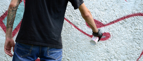A young hooligan paints graffiti on a concrete wall. Illegal vandalism concept. Street art