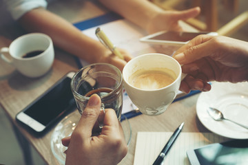 In the meeting time the company's operation, Business team consultations and meeting,summary of sales on table near cup of hot coffee and hand phone.