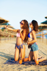 two sexy girls taking selfy on a beach