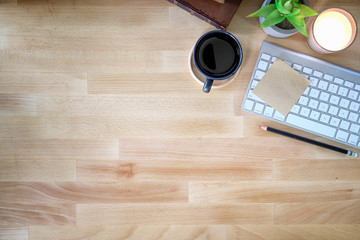 Office desk wooden table with keyboard computer,  cup of coffee and flower. Top view with copy space