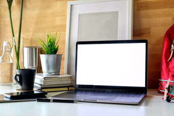 Student workspace laptop, books and mockup poster.