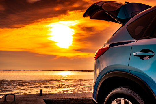 Blue compact SUV car with sport and modern design parked on concrete road by the sea at sunset. Environmentally friendly technology. Road trip travel on vacation at the beach and open car truck.