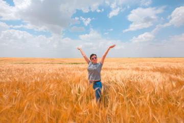 Woman in a golden wheat field on the background cloudy sky