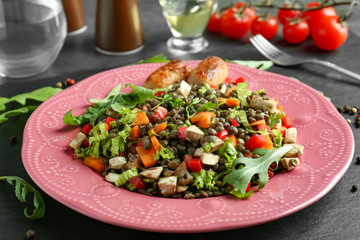 Plate with delicious lentils salad on kitchen table