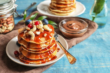 Stack of tasty pancakes with berries, nuts and syrup on table