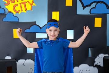 Wall Mural - Cute boy in superhero costume against comic strip themed decoration