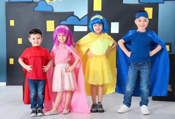 Wall Mural - Cute children in superhero costumes against comic strip themed decoration