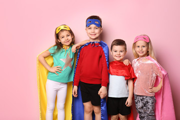 Cute children in superhero costumes on color background