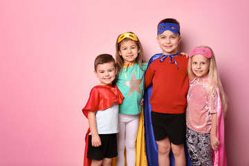Wall Mural - Cute children in superhero costumes on color background