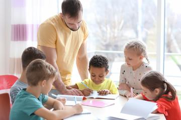 Male teacher helping children with homework in classroom at school