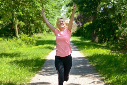 Joyful woman running along a woodland track